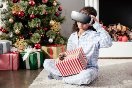 smiling african american child in pajamas using virtual reality headset at home, christmas concept