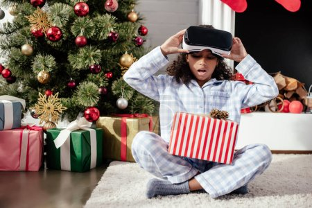 surprised adorable african american child in pajamas and virtual reality headset looking at christmas gift at home