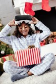 happy adorable african american child in pajamas and virtual reality headset looking at christmas gift at home