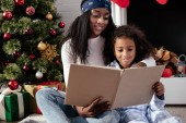 smiling african american mother and daughter reading book together at home, christmas concept