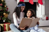 happy african american mother and daughter reading book together at home, christmas concept