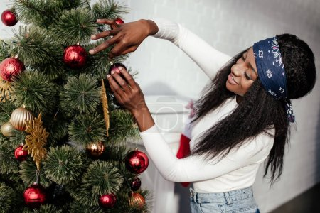 attractive african american woman decorating christmas tree with baubles at home