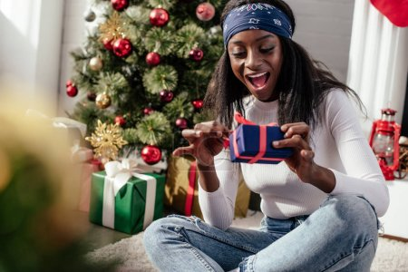 excited attractive african american woman opening christmas gift box at home