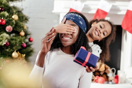 african american daughter gifting christmas present to mother and closing her eyes for surprise at home
