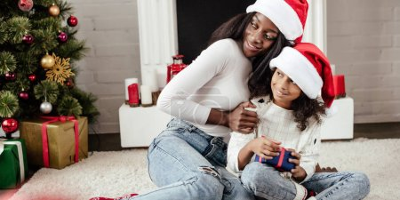 smiling african american mother in santa hat presenting gift to daughter at home and looking away