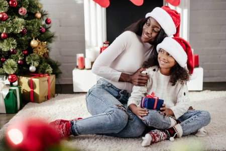 smiling african american woman hugging little daughter with christmas gift in decorated room at home