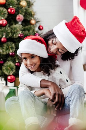 african american mother in santa claus hat hugging little daughter in decorated room at home