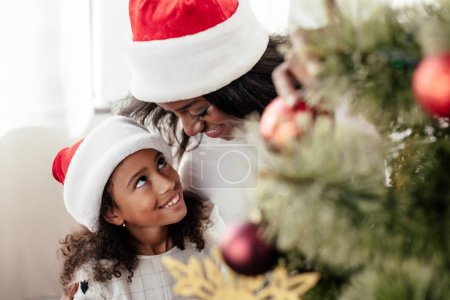 happy african american family in santa claus hats decorating christmas tree together at home
