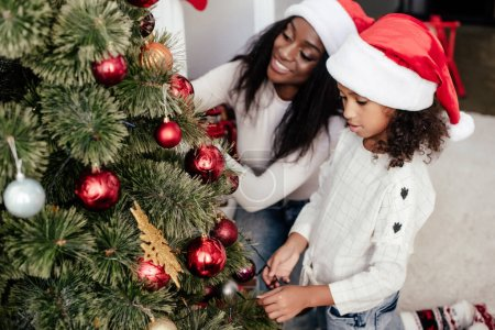 african american mother and daughter in santa claus hats decorating christmass tree together at home
