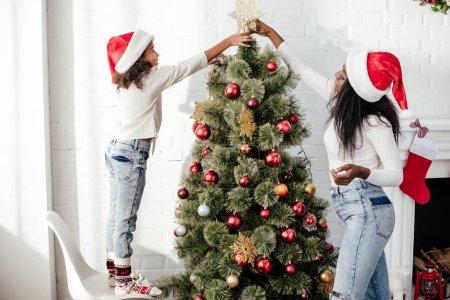 Photo pour Afro-américaine mère et fille chapeaux santa claus décorer arbre de masse ensemble à la maison - image libre de droit
