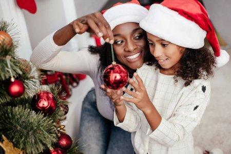 Photo pour Souriant afro-américaine en chapeau de père Noël aider fille pour décorer le sapin de Noël à la maison - image libre de droit