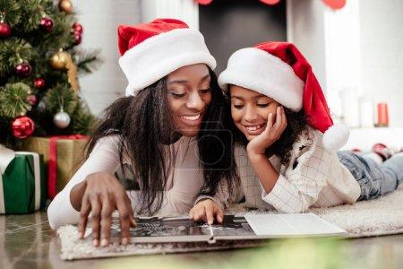 Photo pour Sourire d'une famille afro-américaine en chapeaux de père Noël en regardant album photo dans une salle décorée pour Noël à la maison - image libre de droit