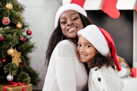 portrait of happy african american mother and daughter in santa claus hats in decorated room at home