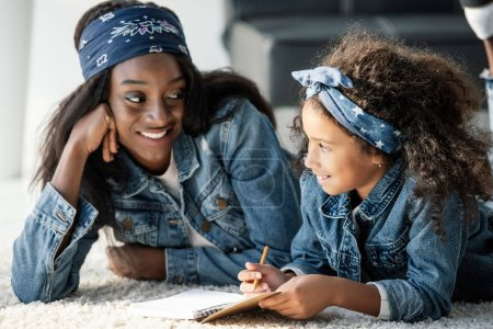 portrait of smiling african american woman helping daughter doing homework at home