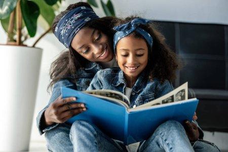 Photo pour Portrait de mère et fille afro-américaine souriante regardant l'album photo de famille à la maison - image libre de droit
