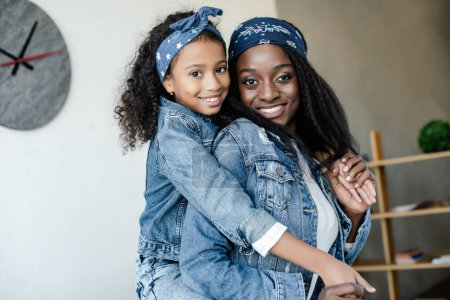 cute african american kid hugging smiling mother in similar clothing at home