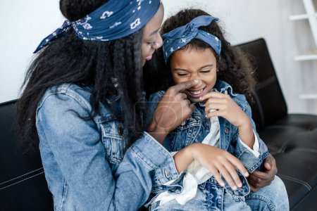 Photo for African american woman and cheerful daughter having fun on sofa at home - Royalty Free Image