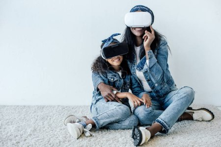 Photo for African american mother hugging daughter in similar clothing and vr headsets at home - Royalty Free Image