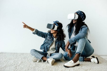 african american mother and daughter in similar clothing and vr headsets at home