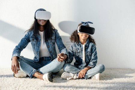 african american mother and daughter in similar clothing and vr headsets holding hands while sitting on floor at home