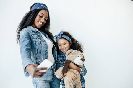 smiling african american woman and daughter in similar clothing taking selfie on smartphone
