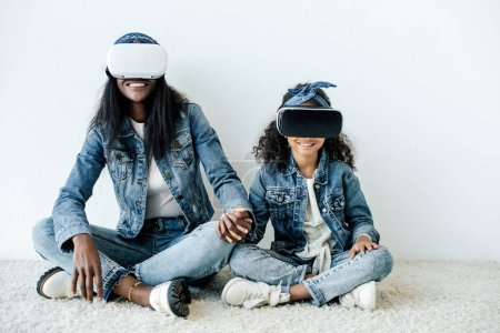 smiling african american mother and daughter in similar clothing and vr headsets holding hands at home