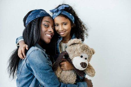 Foto de Retrato de sonriente hija afro americana con madre abrazos de oso de peluche en casa - Imagen libre de derechos