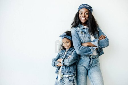 stylish african american mother and daughter in similar clothing posing at wall at home