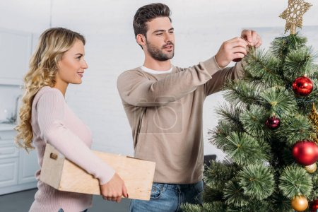 couple decorating christmas tree with baubles together at home, girlfriend holding wooden box with toys