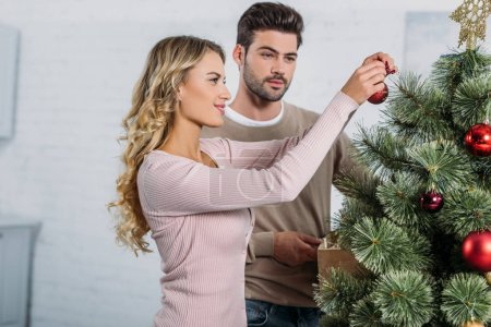 girlfriend and boyfriend decorating christmas tree with baubles together at home