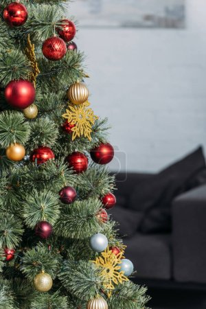 christmas tree with red and golden baubles in living room