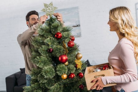 handsome boyfriend decorating christmas tree with star and girlfriend holding wooden box with baubles at home