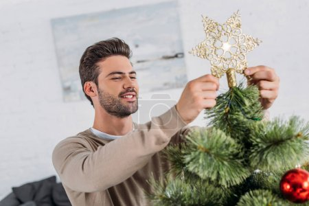 smiling handsome man decorating christmas tree with star at home