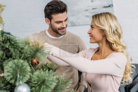 Photo for Happy couple decorating christmas tree with baubles together at home and looking at each other - Royalty Free Image