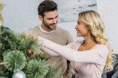 happy couple decorating christmas tree with baubles together at home and looking at each other