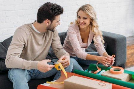 Foto de Sonriente pareja preparando la caja de regalo de Navidad juntos, sosteniendo cintas y mirando el uno al otro en casa - Imagen libre de derechos