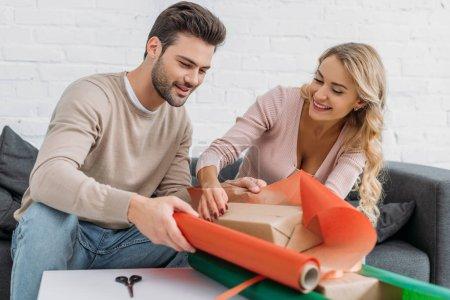 Foto de Feliz pareja preparando la caja de regalo de Navidad juntos en casa - Imagen libre de derechos