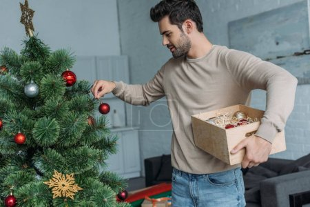 handsome man decorating christmas tree with baubles and holding wooden box at home