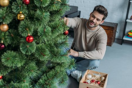 handsome man decorating christmas tree with baubles and sitting on floor at home
