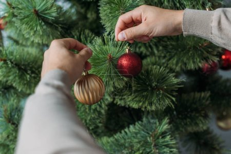 cropped image of man decorating christmas tree with baubles at home