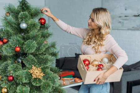 side view of attractive girl decorating christmas tree with baubles and holding wooden box at home