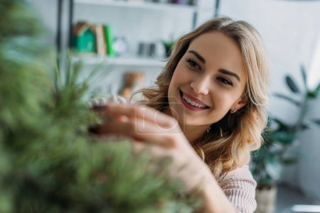 smiling attractive girl decorating christmas tree with baubles at home