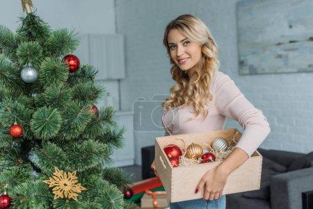 Photo pour Jolie fille décoration sapin de Noël et boîte de portefeuille avec des boules à la maison, en regardant la caméra - image libre de droit