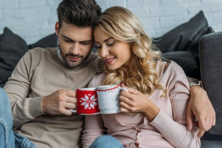 couple clinking with cups of cappuccino at home, christmas concept