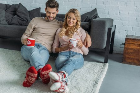 Photo for Smiling couple holding cups of cappuccino and sitting on carpet in living room - Royalty Free Image