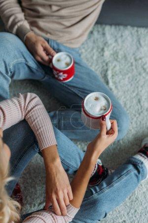 Photo pour Image recadrée de couple assis sur le tapis et exploitation tasses de cappuccino à la maison, notion de Noël - image libre de droit