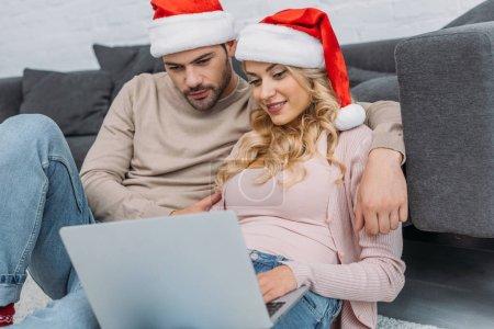 Photo pour Copain et copine chapeaux santa avec ordinateur portable près de canapé à la maison - image libre de droit