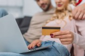 cropped image of couple shopping online with credit card and laptop at home
