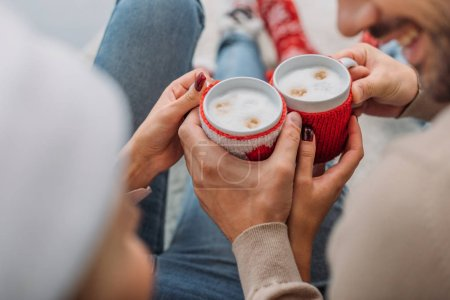 cropped image of couple clicking with cups of cappuccino at home, christmas concept