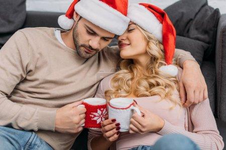 Photo pour Couple affectueux dans chapeaux santa holding tasses de cappuccino à la maison - image libre de droit